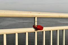 A red metal lock, in the shape of a heart, hangs on the slightly rusty white railing of the river embankment. A railing of a metal. Pipe divides the background royalty free stock photos