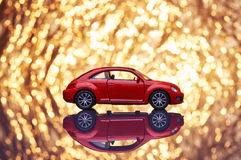 Red metal model car with fancy shiny gold background full of sparks out of focus. Stock Photo
