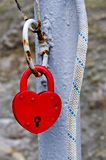 Red metal padlock in a heart shape. Form on a ancient steel tube royalty free stock images