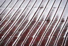 Red metal roof dusted with snow Royalty Free Stock Photos