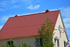 Red metal roof with roof gutter, fascia, ventilation and chimney. House roofing construction. Red metal roof with roof gutter, fascia, ventilation and chimney royalty free stock photo