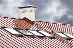 Red metal roof with row of skylights Royalty Free Stock Photos