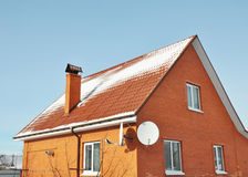 Red metal roof tile and chimney covered with snow Royalty Free Stock Photo