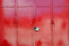 Red metal sheet door was locked with padlock Stock Photo