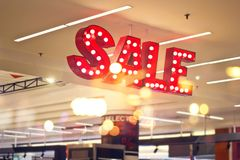 Red metal signage shop lighting on shopping mall background. Red metal signage SALE shop lighting on shopping mall background royalty free stock images