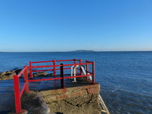 Red metal staircase into the sea. Malahide Dublin Ireland royalty free stock image