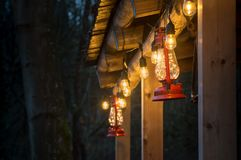 Red metal storm lantern hung outside rustic log cabin. royalty free stock photo