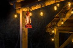 Red metal storm lantern hung outside rustic log cabin. royalty free stock image