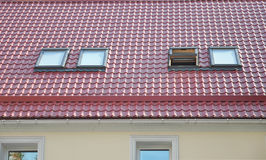 Red Metal tiled Roof with New Dormers, Roof Windows, Skylights, Rain Gutter System and Roof Protection from Snow Board Royalty Free Stock Photography