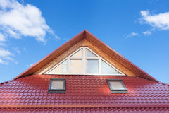 Red Metal tiled Roof with New Dormers, Roof Windows, Skylights and Roof Protection from Snow Board. Stock Photo