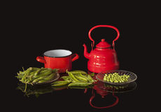 Red metal utensils and peas Stock Photos