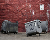 Red metal wall with garbage containers Stock Images