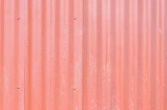 Red metal wall, industrial wall with some ripples and screws. Rusty, painted red and with some bubbles on painting Royalty Free Stock Photography