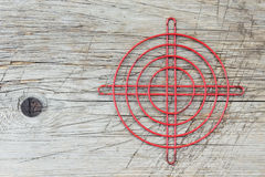 Red metallic crosshair on an old wooden surface Stock Images