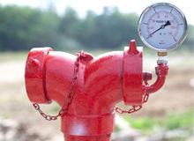 Red metallic fire hydrant with pressure gauge or Fire Department. Connection on street royalty free stock photography