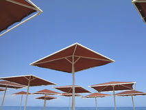 Red metallic parasol beach umbrellas over blue sky Stock Photo