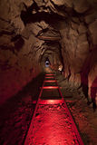 Red Mine Tracks. Underground in an abandoned mine with red lit ore cart tracks royalty free stock image