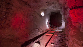 Red Mine Tracks Underground. Underground in an abandoned mine with red lit ore cart tracks and walls royalty free stock images