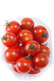 Red mini tomatoes in packaging. Red cherry tomatoes packaged for sale. white background Stock Photos