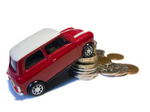 Red mini toy car against pile of British coins stock images
