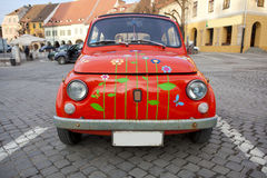 Red mini vintage car; Red Bug. A red mini vintage car with butterflies and flowers painted on it. The car is situated in the center of Hermannstadt (Sibiu) in royalty free stock images