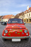 Red mini vintage car; Red Bug. A red mini vintage car with butterflies and flowers painted on it. The car is situated in the center of Hermannstadt (Sibiu) in royalty free stock photography