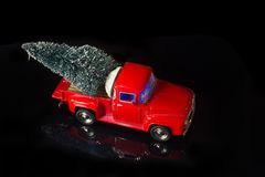 Christmas background with Red vintage truck deliver Christmas tree on its back. Red miniature vintage truck deliver Christmas tree on its back on black stock photos