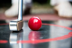 Red minigolf ball and an iron racket at a minigolf court Royalty Free Stock Photos