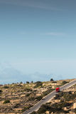 A red minivan driving down a hill in the Maltese countryside, ju. St outside of Mellieha. Malta, 8th January 2017 Stock Photos