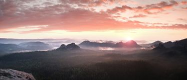 Red misty  landscape panorama in mountains. Fantastic dreamy sunrise on rocky mountains.  Foggy misty valley below Royalty Free Stock Photos