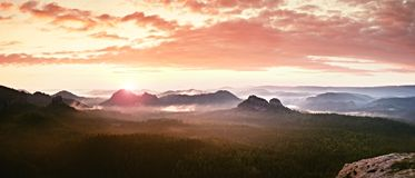 Red misty  landscape panorama in mountains. Fantastic dreamy sunrise on rocky mountains.  Foggy misty valley below Royalty Free Stock Images