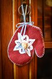 Red Mitten Christmas Ornament with Blue Ribbon. A homemade, felt, red mitten Christmas ornament with a light blue ribbon hanging on a knob stock photo