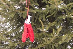 Red mittens with paper dog figure on fir tree branches. Red mittens with paper dog figure on fir tree green branches stock images