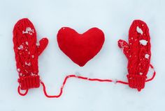 Red mittens and plush decorative heart on snow stock image