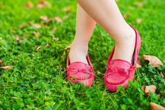 Red moccasins on childs feet Royalty Free Stock Image