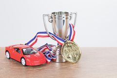 Red model supercar with a trophy and medal. In a concept of wining a championship motor race or competition with copy space alongside royalty free stock photography