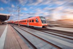 Red modern high speed train in motion. On railroad track at sunset in Europe. Train on railway station with motion blur effect. Industrial landscape with train royalty free stock image