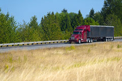 Red modern semi truck and black tarp trailer Royalty Free Stock Image