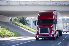 Red modern semi truck with reefer trailer under bridge Royalty Free Stock Photo