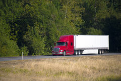 Red modern semi truck and trailer summer high way Stock Photo