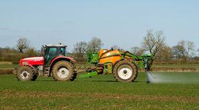Red modern tractor pulling a crop sprayer Stock Images