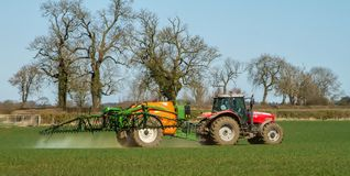 Red modern tractor pulling a crop sprayer Stock Photo
