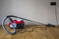 Red modern vacuum cleaner with black electric cable on wooden pa Stock Photos