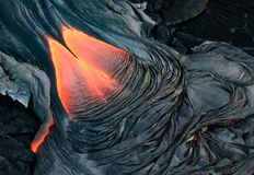 Red molten lava slowly moves across land, solidifying as it cool royalty free stock photo