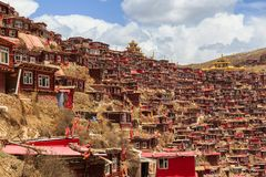 Red monastery and home at Larung gar Buddhist Academy in sunshine day and background is blue sky. Sichuan, China Royalty Free Stock Photo