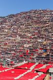 Red monastery at Larung gar Buddhist Academy in sunshine day and background is blue sky. Sichuan, China Stock Photo