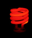 Red Money Saver Light. A red compact flourescent energy saver light bulb set against a black background Stock Images