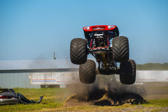 Red monster truck. Jumping high in the air, looking under the truck more than the side or top. Dirt flying over n the air from the truck royalty free stock photo