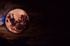 Red moon. Moon by night, the clouds giving this effect are very attractive, underlined by the red colour of the moon Royalty Free Stock Photography