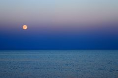 Red Moon and blue sea at nightfall Royalty Free Stock Image